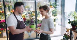 Fiorista maschio che tiene pianta verde che parla con cliente femminile nel deposito di fiore stock footage