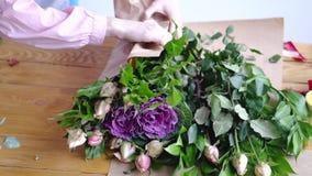 Fiorista professionista che avvolge i fiori in carta al negozio di fiore archivi video