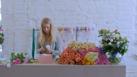 Fiorista professionista che fa il contenitore di regalo con i fiori al deposito di fiore stock footage