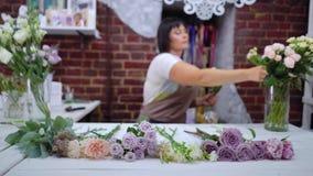 Fiorista professionista Defocused che seleziona branche rosa per la disposizione dei fiori nello studio di progettazione floreale stock footage