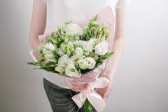 Fiorista sul lavoro Faccia il mazzo del lisiantus bianco Fondo floristico d'annata, rose variopinte, forbici antiche ed a Fotografia Stock