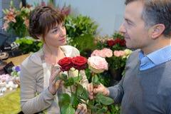 Fiorista supplichevole sorridente che dà le rose del mazzo al cliente Immagini Stock