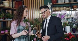 Fiorista sveglio che descrive le belle piante verdi all'uomo barbuto nel negozio di fiori video d archivio