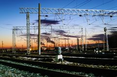 Fios de alta tensão acima das trilhas de estrada de ferro Céu bonito do por do sol imagens de stock royalty free