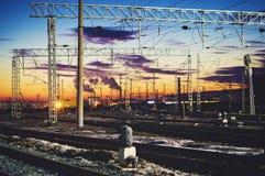 Fios de alta tensão acima das trilhas de estrada de ferro Luz bonita do por do sol fotos de stock royalty free