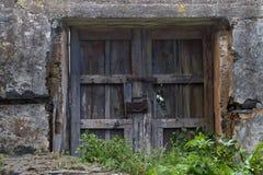 Fios de madeira velhos da porta ou da porta e de metal do fechamento oxidado Fora da casa, a vila, tudo entra a ruína Imagem de Stock Royalty Free