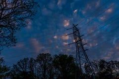 Fios de tensão alta cercados por árvores e um céu azul com nuvens inchados foto de stock royalty free