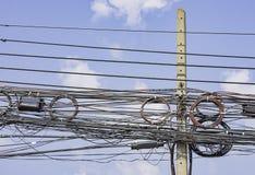 Fios elétricos e cabos que penduram em uma coluna concreta e no céu azul brilhante imagens de stock