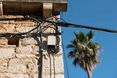 Fios elétricos unidos em uma casa de pedra velha Edifício redondo Transmissão da eletricidade Ampola na construção Ligh da rua imagens de stock