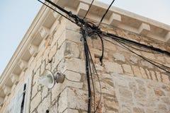 Fios elétricos unidos em uma casa de pedra velha Edifício redondo Transmissão da eletricidade Ampola na construção Ligh da rua fotografia de stock royalty free