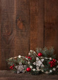 Fir branch with Christmas decoration on wooden plank. Royalty Free Stock Photo