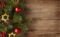 Fir branch with Christmas decorations on the background of  old grunge wooden board Royalty Free Stock Photos