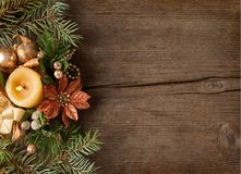 Fir branch with Christmas decorations and candle on the background of old wooden plank Stock Image