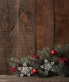 Fir branch with Christmas decorations on  rustic  wooden background. Stock Image
