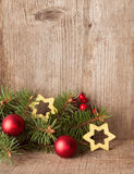 Fir branch with Christmas decorations on rustic wooden background Stock Photo