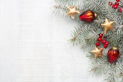 Fir branch with Christmas decorations on white rustic wooden background with copy space for text.  stock photography