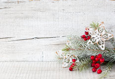 Fir branch with Christmas decorations on   white rustic wooden background. Royalty Free Stock Image