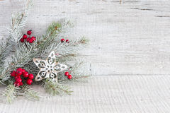 Fir branch with Christmas decorations on white rustic wooden background. Stock Photos