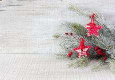 Fir branch with Christmas decorations on white rustic wooden background Royalty Free Stock Images