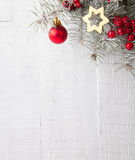 Fir branch with Christmas decorations on the white wooden plank. Stock Photo