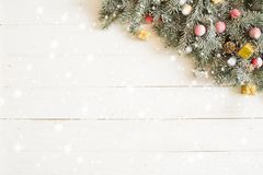 Fir branch with Christmas decorations on the white wooden table or plank background Stock Image