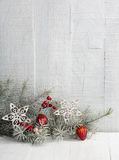 Fir branch with Christmas decorations on wooden plank. royalty free stock images