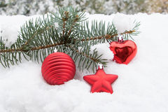 Fir branch with Christmas toys in the snow Royalty Free Stock Photo