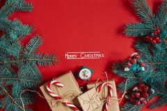 Fir branch and gift box on red background. The inscription - Merry Christmas. Fir branch and gift box on red background. Top view. Flat lay. Copy space. Still Stock Images
