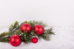 Fir branch with red christmas balls in snow Royalty Free Stock Photography