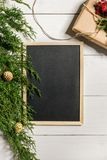 Fir branches border and black chalk board on white wooden background, good for christmas backdrop. Free space for text. top view. Copy space. Closeup Stock Images