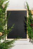 Fir branches border and black chalk board on white wooden background, good for christmas backdrop. Free space for text. top view. Copy space. Closeup Royalty Free Stock Photo