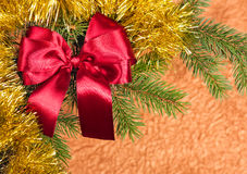 Fir branches with bow on golden background Royalty Free Stock Photo