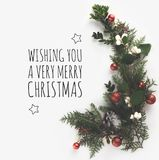 Fir branches with christmas balls. Top view of christmas fir branches, christmas balls and pine cones with Wishing you a very merry christmas lettering, isolated royalty free stock photo