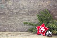 Fir branches and Christmas star on wooden background. Royalty Free Stock Images