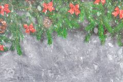 Fir branches with cones and red bows on top of a gray concrete background. New Year Christmas. Free space for text. Fir branches with cones and red bows on top Stock Photography