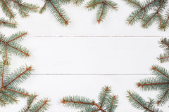 Fir branches in form of frame on white wooden table. Christmas and Happy New Year composition.Flat lay, top view Royalty Free Stock Photo