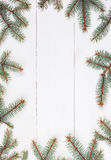 Fir branches in form of frame on white wooden table. Christmas and Happy New Year composition.Flat lay, top Stock Photos