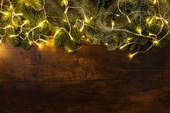 Fir branches with garland. From above Christmas tree branches with colorful cozy garland illumination on wooden background Royalty Free Stock Images