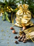 Fir branches on the grey concrete background with gold stars. New Year Christmas. Gold bag of nuts Stock Photo