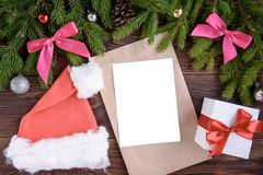 Fir branches, pink ribbon bow, Christmas cap, envelope and christmas balls. New Year background. stock image