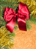 Fir branches with red bow on golden Royalty Free Stock Photo
