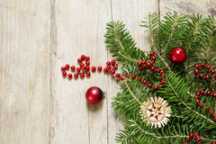 Fir branches with red christmas baubles and straw star on rustic Royalty Free Stock Photography