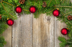 Fir branches with red ornaments and cones on rustic wooden board Royalty Free Stock Photo