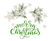 Fir branches in the snow on a white background and text of Merry Christmas. lettering calligraphy.  Stock Images