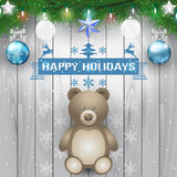 Fir branches, teddy bear and christmas light bulb on wooden background Royalty Free Stock Photography
