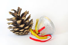 Fir cone and bell on white Stock Photos