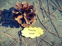 Fir-cone, dry spruce needles and paper note Time To Travel on the ground Stock Photos