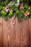 Fir tree branch with christmas lights and candy canes on wood Stock Image