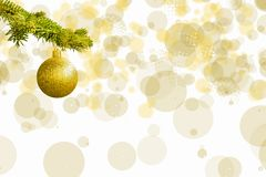 Fir tree branch with a golden glitter ball on white background. Bokeh effects. Christmastime. Christmas postcard. With white espace fot text royalty free stock photography