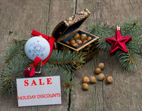 Fir-tree branch with an ornament, a casket with nutlets and a la. Bel Festive Sale, on a wooden table, a subject holidays Christmas and New Year stock photography